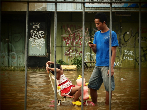Photo 04. Resident in East Jakarta using a mobile device during monsoon flooding; January 2014. Photography by Ariel Shepherd.